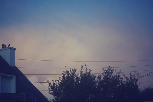 Matin breton 2 / Image illustrant l'article. Photo d'un ciel breton, retouchée, avec un bout de toit de maison avec cheminée, des arbres, ciel bleu et nuages rosés.