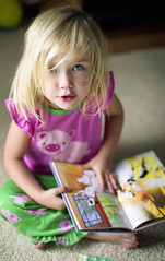 telling stories (manyfires) Tags: portrait film girl book pig child iowa niece alaina 101dalmations nikonfm blondhairandblueeyes donotruninthefamily ahthepowerofgenetics andrecessivegenes