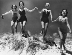 Young women running over a sand dune on an unidentified beach, ca. 1935 (State Library of Queensland, Australia) Tags: statelibraryofqueensland slq bathingbeauties swimsuits women four smiles holdinghands 1930s beach sand commons:event=commonground2009 orale gluecksmomente maillot swimsuit swimwear bathingsuit queenslandaustralia funatthebeach carefree queensland allureandbeauty dunes bathingcap running