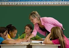 Profesora en pie, alumnas sentadas
