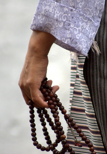 A Tibetan Lady Prays With Her Mala (Beads)
