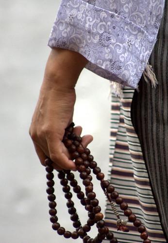 A Tibetan Lady Prays With Her Mala (Beads)