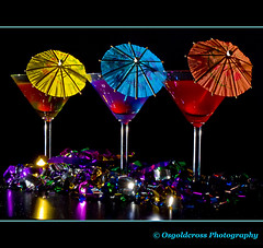 Cocktails For Three (Osgoldcross Photography) Tags: blue red abstract macro green yellow glitter umbrella silver studio gold glasses cherries raw colours arty purple bokeh flash olympus explore parasol tinsel cocktails umbrellas homestudio explored rawconversion strobist olympuse420 interestingness110on270809