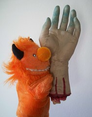 Helix catches a creepy hand! (helixdmonster) Tags: orange monster puppets helix handpuppets severedhand creepyhands monsterhandpuppets helixdmonster