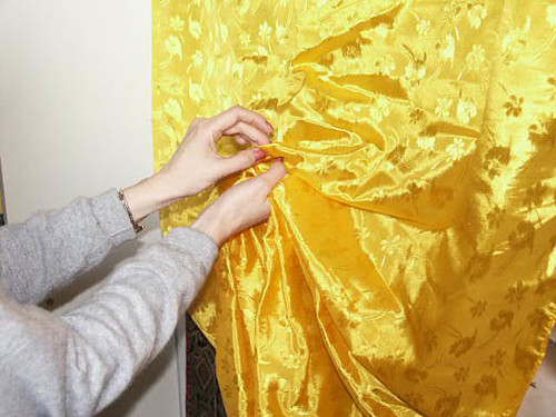 Continue gathering the silk, folding it back and forth in your hand, until you reach the top of the thangka mounting.