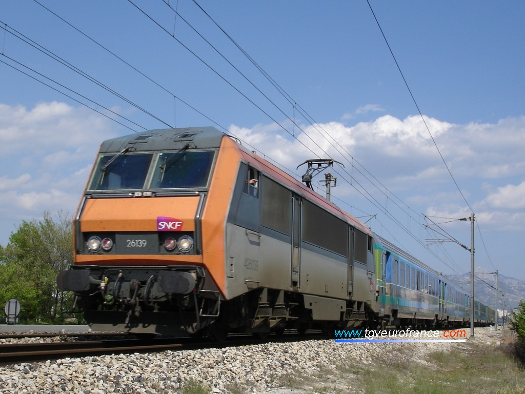 Une locomotive bi-tension BB26000 avec le nouveau logo SNCF se dirige vers la gare de La Penne-sur-Huveaune le 25 avril 2006.