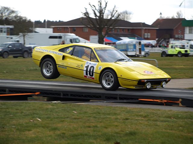 Yellow Ferrari 308GTB rally car landing from a jump