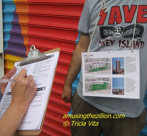 Save Coney Island volunteer collecting signatures on Mermaid Parade Day in Coney Island. Photo © Tricia Vita/me-myself-i via flickr