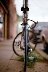 roadie (Ansel Olson) Tags: road street blue sky urban black cars grass bike bicycle wheel sign buildings virginia fan nikon dof post kodak bokeh lock seat richmond sidewalk va storefront pedals f3 gears curb 160vc portra kryptonite 50mmf14 rva derailleur richmondcity bikeh autaut