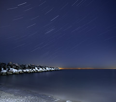Cold Island Beach with Star Trails (Mute*) Tags: longexposure light lake toronto cold ice beach water night stars island rocks nightshot freezing pollution lakeontario groyne canonef1740mmf4lusm startrails vertorama