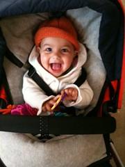 Laila chortling in her stroller