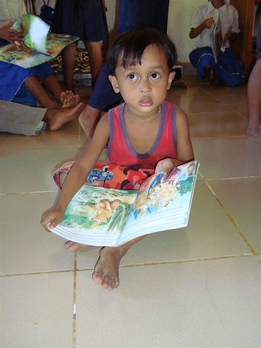 Even the youngest students enjoy the colorful picture books provided by Room to Read.
