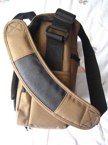 One side of the Tamrac with the shoulder strap draped across. You can see that the shoulder piece is curved and padded, and the black stuff gives the strap extra grip on your shoulder. The strap links to the bag with plastic attachments.