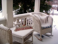 front porch with six inches of white snow on the chairs and railing