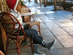 Waiting for the Rain (Lynn Friedman) Tags: fillmorest lowerhaight sanfrancisco squatgobble restaurant outdoorcafe rainboots santahat child lynnfriedman friedmanlynn wickerfurniture sidewalkcafe sidewalk 94117 sfist ca california usa rain streetsandpeople streets sf impressionistic painterly theme blur
