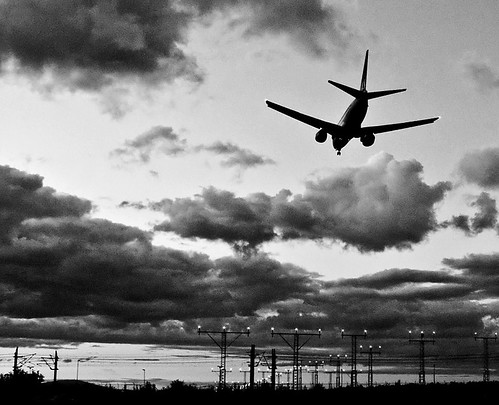 A grainy black and white photograph of an airplane over an airport.