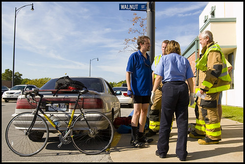 Cyclist Jeff Wainright talks with Columbia emergency responders after colliding with MU student and motorist Dan Marston on Tuesday afternoon in downtown Columbia. Wainright, who rolled over Marstons car hood, suffered only minor scrapes and bruises.