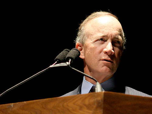 Mitch Daniels, a white man, stands at a podium. He is wearing a suit and tie.