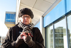 Text Woman (debfreemansmudge) Tags: street reflection scarf buildings phone close cigarette gloves hastings texting berret cigarettesmoke blackglasses leicam8