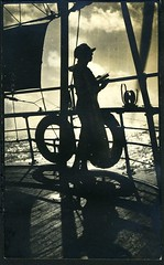 Photo On Heavy Stock: Woman Onboard Ship, In Silhouette (mrwaterslide) Tags: ocean old shadow sea woman cloud sun hat silhouette clouds vintage found book waves ship antique album deck oldphoto vernacular railing breeze lifepreserver shipboard