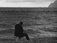 man and the sea (kyramas) Tags: sea sky bw man beach water rio clouds pentax greece lonely sigma1770 k100d