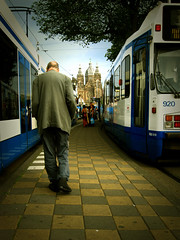 Tram Station (Vineyards) Tags: people church amsterdam composition walking colours candid religion perspective citylife streetphotography dramatic oldman transportation streetphoto publictransport juxtaposition centralstation sintnicolaaskerk chessboard streetshot openbaarvervoer tramstation tramhalte churchofstnicholas schaakbord straatfotografie number920