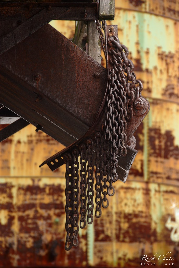 A rusted rock chute, pointing down at an angle, with chains hanging around it and a rusted yellow background.