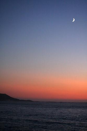 Lúa nova en cabo Silleiro, no solpor atlántico
