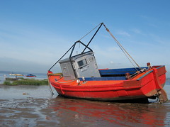 Blue skies, red boat