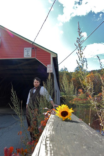 groom in front of covered bridge