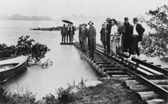 Group of men standing on the flooded railway bridge over the Burdekin River, 1917