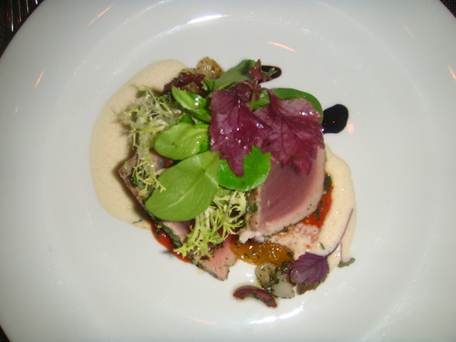 Grilled Yellow Fin tuna with citrus herb crust, oven cured tomatoes, kalamata olives and roasted pepper puree