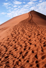 An uphill struggle! Dune 45, Namibia (Marjan de B) Tags: africa travel red vacation sky people orange clouds sand october desert footprints dry namibia 2009 sossusvlei namib southernafrica dune45 namibnaukluft deblaauwpix