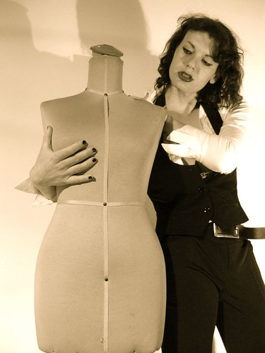 A person with medium-length curly hair, wearing black pants with a belt, a white shirt, a black waistcoat, lipstick and nail polish. They are holding onto a headless, unclothed mannequin as though working with it.