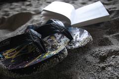 Where? (Elios.k) Tags: summer beach reading book sand focus dof open greece pebble page flipflops