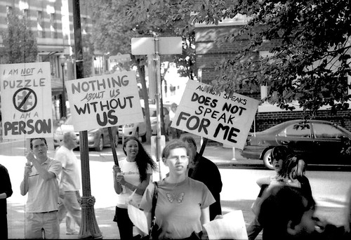 black and white photo of protesters holding signs reading 'i am not a puzzle i am a person', 'autism speaks does not speak for me' and 'nothing about us without us'