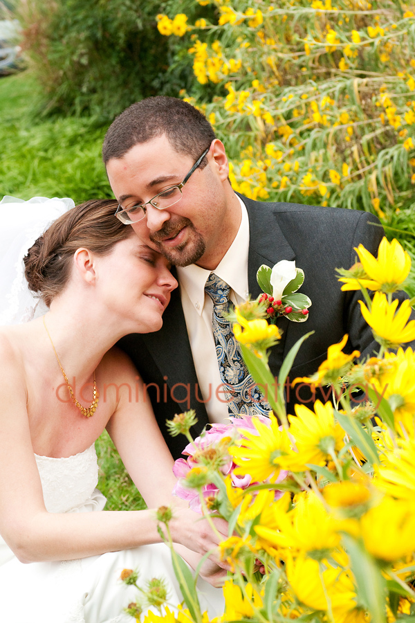 newly wed couple by flowers