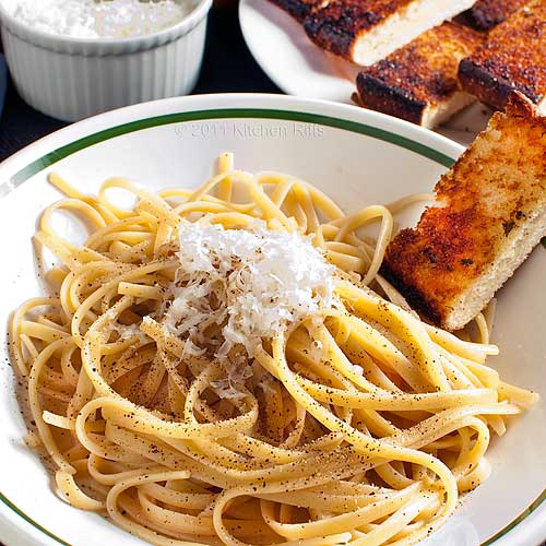 Pasta Cacio e Pepe (Romano cheese and black pepper) in bowl with garlic bread garnish