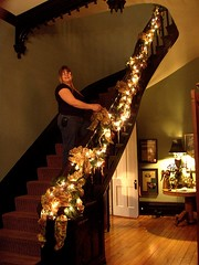 therersa standing on the entrance staircase with roping and lights going up the banister