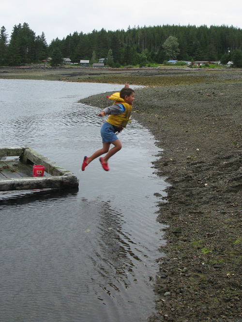 a boy jumps to shore at low tide, Kasaan, Alaska