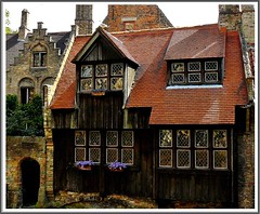 Oldest wooden house, Bruges (jackfre2 (on a trip-voyage-reis-reise)) Tags: wood flowers windows house arch bricks stainedglass led roofs tiles bruges portal woodenhouse chimneys blueribbonwinner supershot mywinners aplusphoto colourartaward