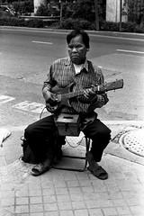 "Les Paul Thai style - Bangkok, city of angels (Sailing ""Footprints: Real to Reel"" (Ronn ashore)) Tags: life street people blackandwhite men film musicians portraits faces blind traditional poor blues buskers blindness sightless agfaapx400 nikonfm2n nikkor50mmf12ais bangkokcityofangels 2009july0029fm2n50mmf12aisagfa400apxbkk"