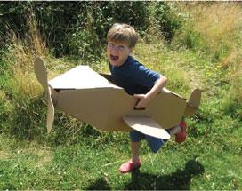 criança aviao de papelão
