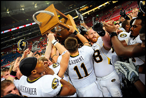 Missouri senior wide receiver Danario Alexander, sophomore quarterback Blaine Gabbert and graduate student offensive lineman Kurtis Gregory celebrate Missouris win on the field with the Arch Rivarly trophy.