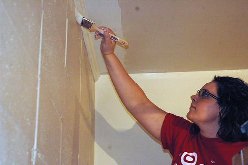 A Target employee paints the wall in the new Salvation Army Media Library.