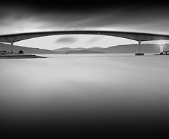 OVER THE SEA....(explore) (kenny barker) Tags: bridge light sea bw lighthouse skye water monochrome landscape scotland dusk panasonic le g1 lochalsh greatphotographers artdigital saariysqualitypictures exoticimage