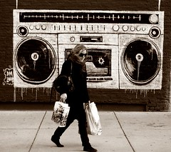 woman walking in front of a tape recorder mural
