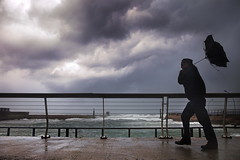 Walking againts the wind (Gilad Benari) Tags: ocean winter sea man art wet rain weather silhouette clouds umbrella print harbor israel telaviv upsidedown wind rail stormy  twisted strom gilad  strongwind     heavyclouds pster    againts benari     israeliwinter