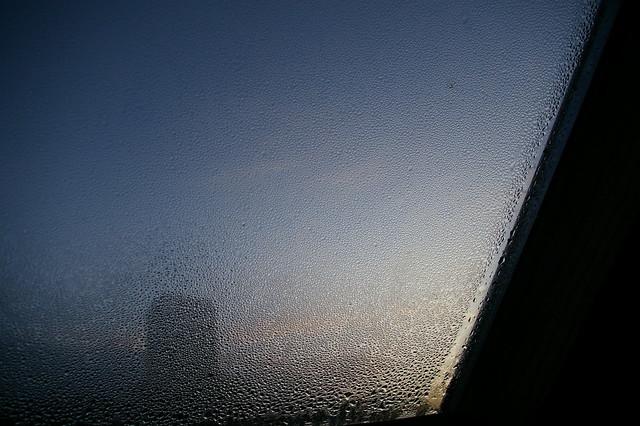 Matin breton 4 / Image illustrant l'article. Photo du coin inférieur droit d'un vélux avec de la condensation. Une cheminée en transparence.