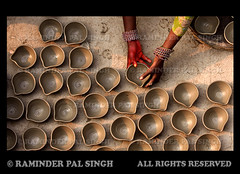 Arranging The Lamps (Raminder Pal Singh) Tags: light india festival canon pattern earth faith religion potter dry lamps punjab diwali festivaloflights amritsar creamofthecrop afc hindufestival bangles rituals diyas diya indiafestival canonshot workingwoman raminder womanworking earthenlamps topangle topimages bestphotography raminderpalsingh shotwithcanon ladyworking unseenindia earthenwarelamps womanpotter potterslife womanworkingonearthenlamps womanputtinglamps canontopshot photographicrepresentationofpatterns